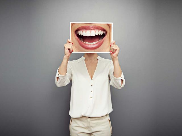 Woman holding up smile shutterstock