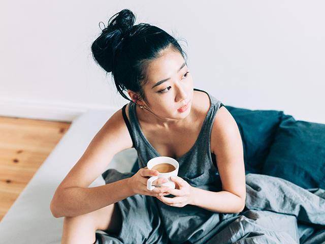 Woman with anxiety drinking coffee in bed
