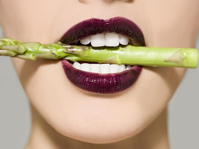 Woman with asparagus in mouth