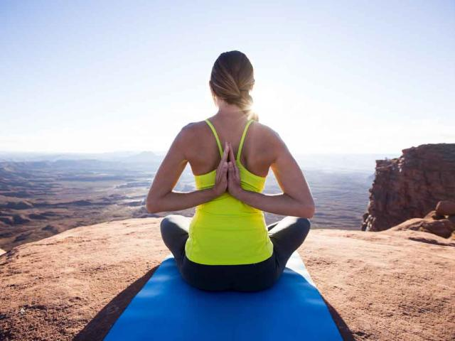 Yoga woman on mountain - healthy intentions - energising yoga moves - womens health