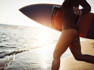 Woman with surf board running into sea
