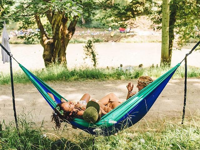 Friends relaxing in hammock at wilderness festival
