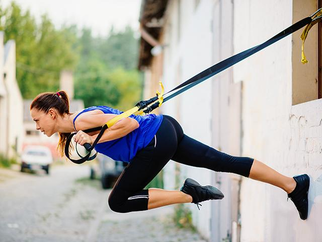 Girl getting better at pull ups using a trx - Women's Health UK