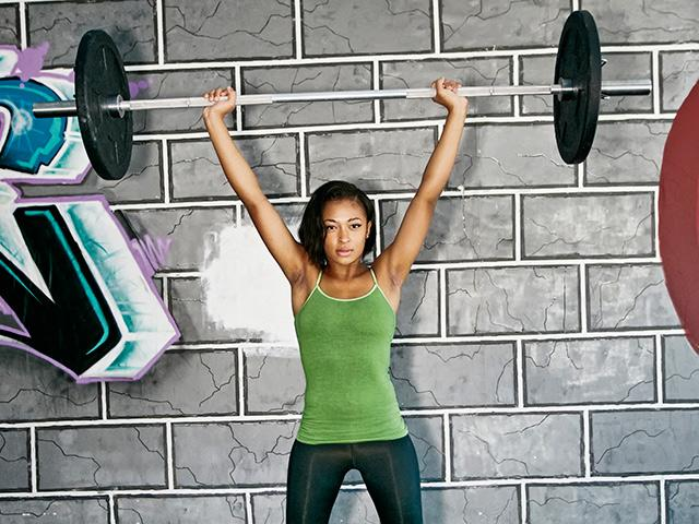 Woman lifting barbell above her head