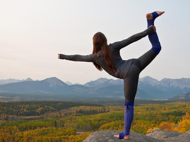 Woman-doing-yoga-on-cliff-shutterstock