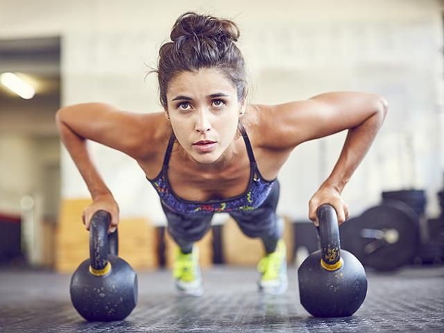 Portrait of female doing kettlebells in training gym
