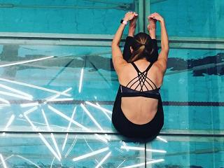 Back extension fitness tests leaning over swimming pool showing sports bra detail - womens health uk