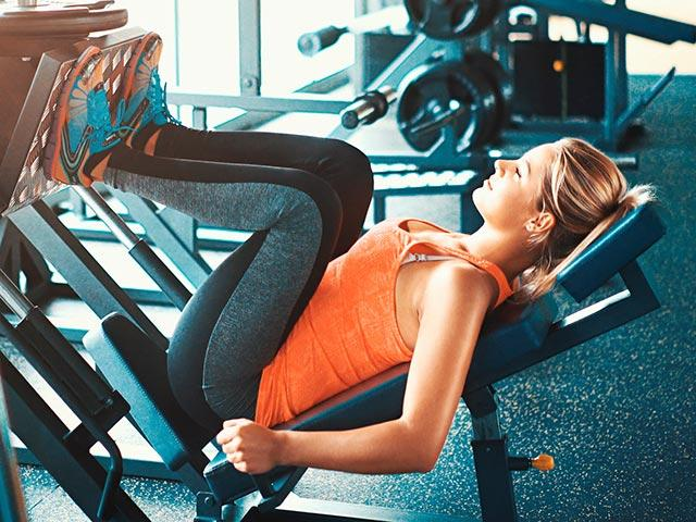 Woman on a leg press in the gym, how to train harder