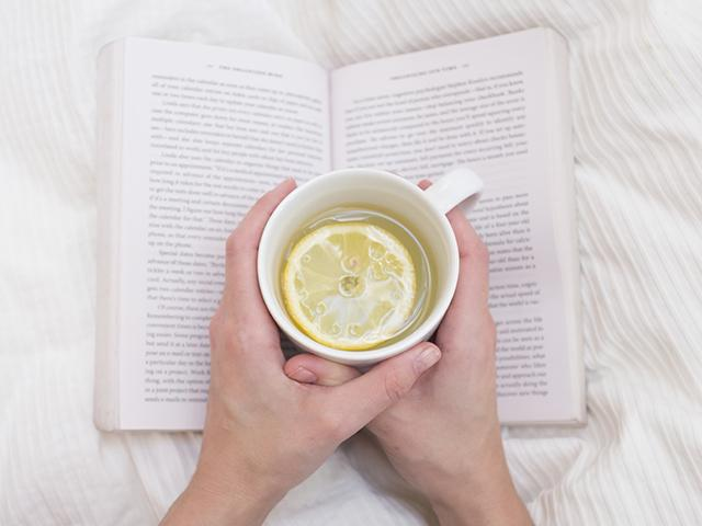 Lemon water in a mug with a book