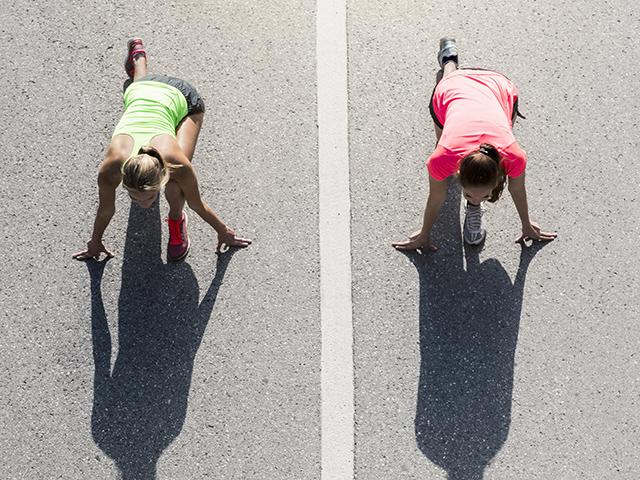 Two women on start line for race pushing each other
