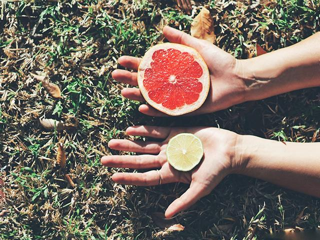 Grapefruit and lime in womans hands outside in natural setting