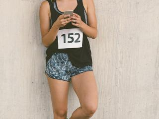 Woman ready for marathon race looking at phone