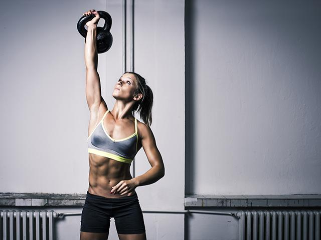 Woman with abs doing kettlebell exercises