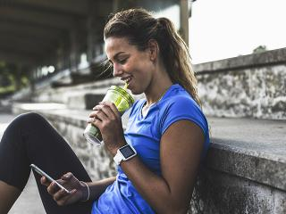 Woman next to track looking at phone drinking smoothie