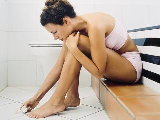 Woman painting her nails in the bathroom