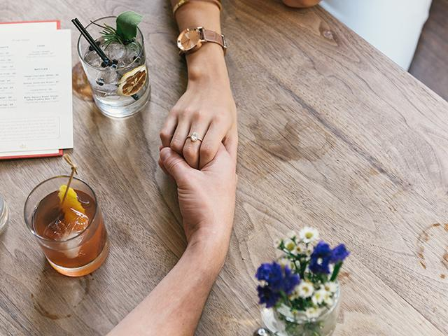 Couple dating holding hands over drinks
