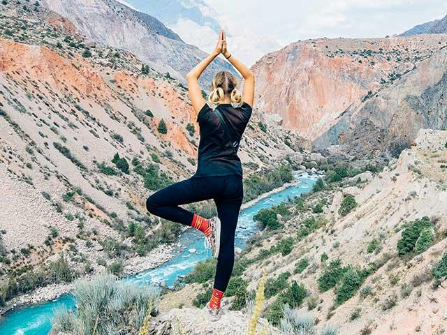 Outdoor activities - woman walking on cliff in keen footwear