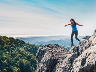 Outdoor activites - woman walking on cliff in keen footwear