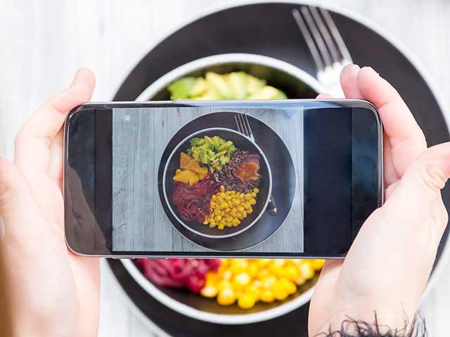 Girl taking picture of salad bowl with smartphone