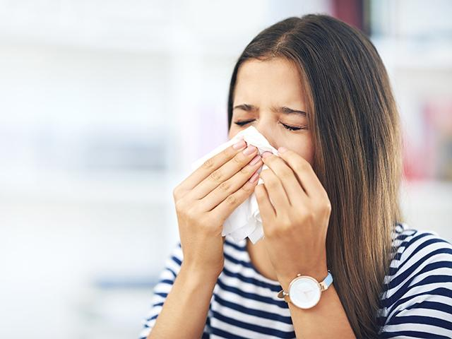 Woman sneezing with hay fever symptoms