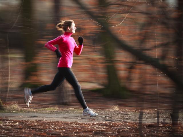 Woman running through a wood in autumn shutterstock