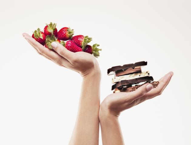 Strawberries and chocolate weighed in womans hands - 103332766