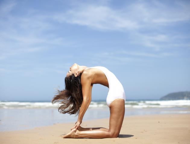 Woman doing yoga on beach - 166844753