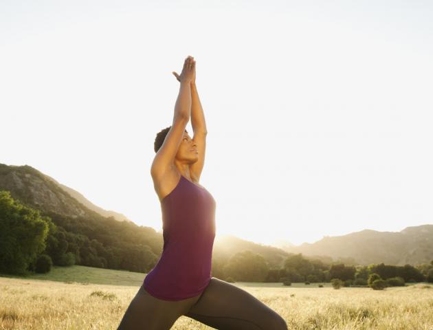 Woman doing yoga sun salutation outside - 135537881