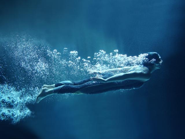 Woman swimming in dark pool shutterstock