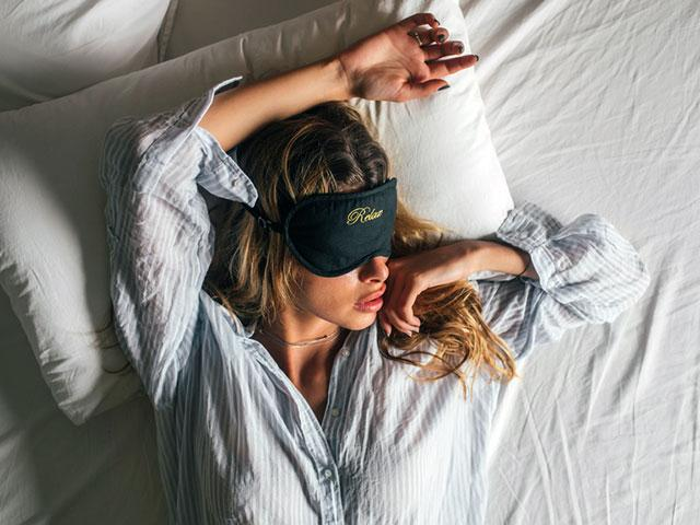 Woman sleeping with face mask - How To Get More Sleep - Women's Health UK