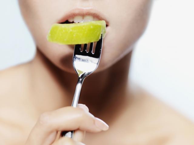 Woman eating segment of fruit - 116780414